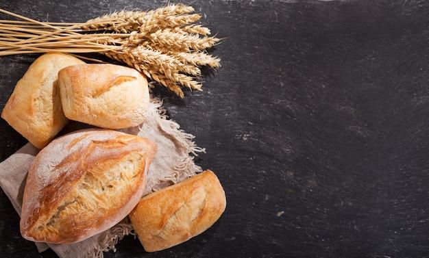 暗いテーブル、上面図に小麦の穂と焼きたてのパン
