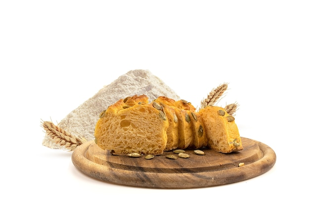 Fresh bread on a wooden board and wheat flour