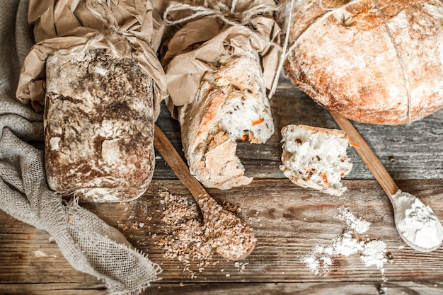Fresh bread and wooden spoon on old wooden background