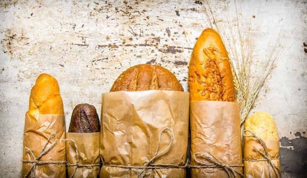 紙で包んだ焼きたてのパン。素朴な背景に。上面図