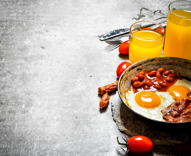 Fresh breakfast bacon with fried eggs and beans orange juice and tomatoes on the stone table