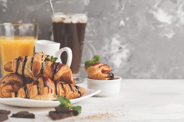 Fresh breakfast croissants with chocolate syrup, orange juice and cocoa with marshmelow. copy space. french cuisine dessert concept.