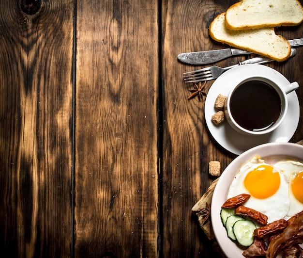 作りたての朝食。一杯のコーヒー、卵と燻製ソーセージと一緒に揚げたベーコン。木製の背景に。