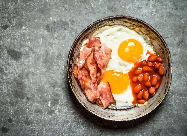 新鮮な朝食石のテーブルに卵と小豆を添えた揚げベーコン
