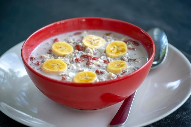グラノーラ、ヨーグルト、ナッツ、ゴジベリー、チアシード、バナナの作りたての朝食。赤いボウルにフルーツとベリーのミューズリー、クローズアップ