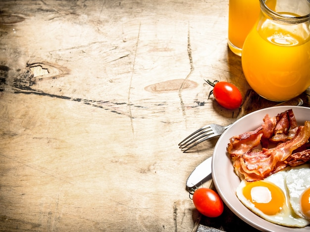 Fresh breakfast. orange juice with fried eggs, bacon, and slices of bread. on a wooden table.