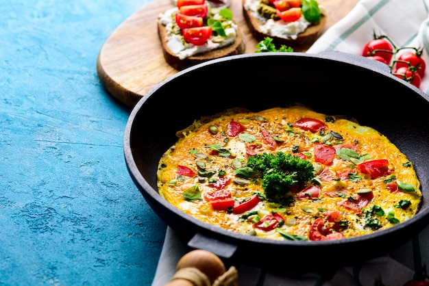 Fresh breakfast in the pan. omelette with greens and tomatoes, sandwiches with cream cheese, pesto and cherry tomatoes on a turquoise background with copy space