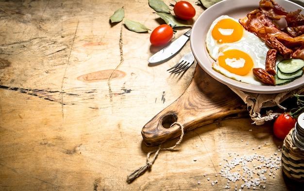 Тарелка свежего завтрака яичница с беконом и помидорами на деревянном столе