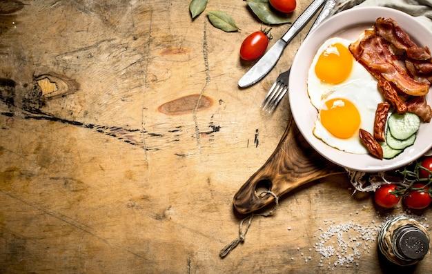 新鮮な朝食プレート。ベーコンとトマトの目玉焼き。木製のテーブルの上。