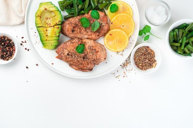 Свежий завтрак с авокадо и жареной грудкой с фасолью на белом фоне. вид сверху, с местом для копирования. понятие о диетических блюдах.