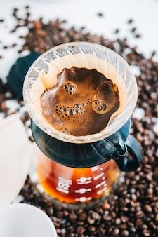 드립퍼와 종이 필터 위에 붓는 대체 방법을 사용하여 컵에 갓 내린 커피.