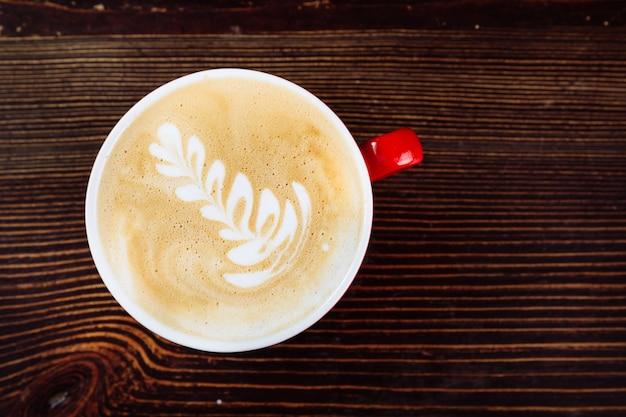 Свежезаваренный кофе с латте-арт в красной чашке крупным планом