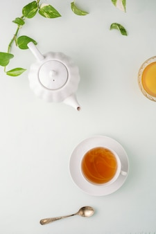 Fresh brewed tea, teapot and honey on a light table. white dishes. light background.