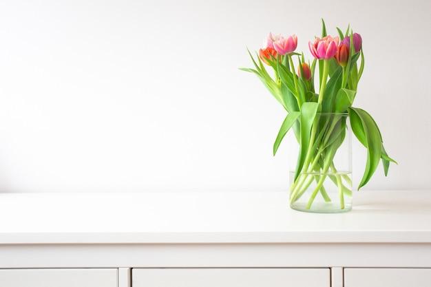 Свежий яркий букет красочных тюльпанов возле белой стены на деревянной полке в стеклянной вазе с пространством для текста