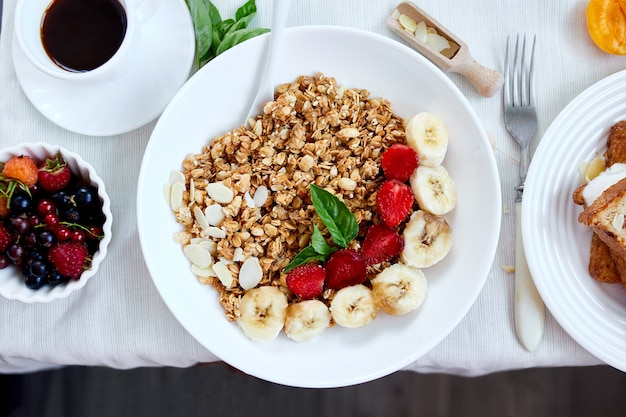 Fresh and bright continental breakfast table, abundance healthy meal variety crunch cereal, french toast, fruits, lemonade, coffee, croissant on  table served