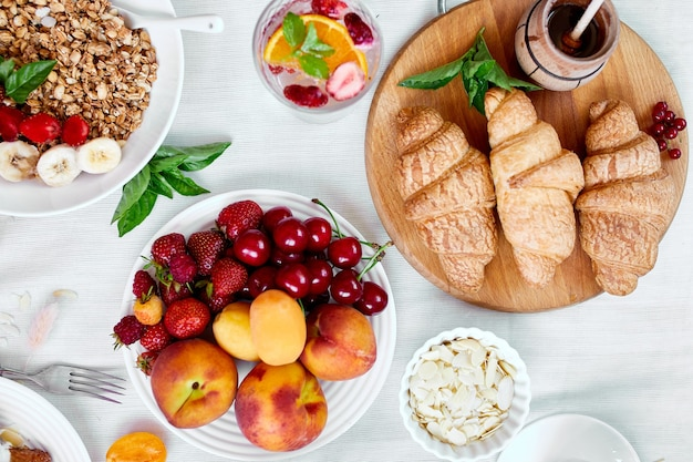Fresh and bright continental french breakfast table, abundance healthy meal variety crunch cereal, fruits, lemonade, coffee, croissant on  table served, top view, flat lay, copy space, frame.