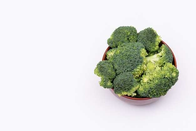Пук свежей брокколи зеленого брокколи в коричневой керамической миске, изолированные на белой поверхности