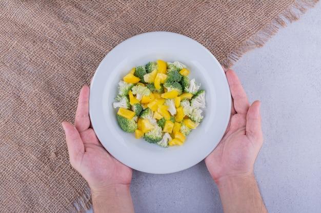 Broccoli freschi, cavolfiori e peperoni gialli mescolati in un'insalata su fondo marmo. foto di alta qualità