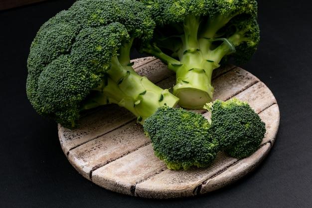 Fresh broccoli on cutting board on black surface