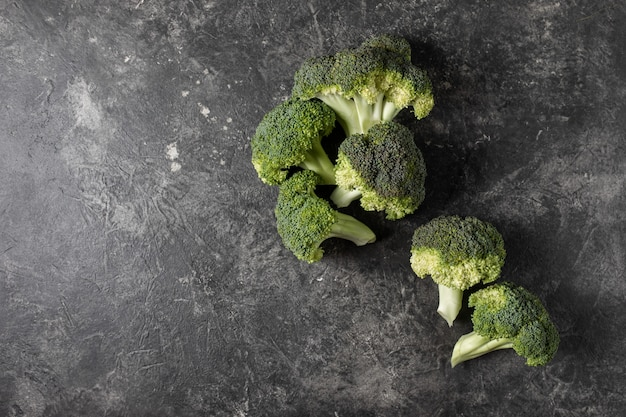 Fresh broccoli on a dark table, top view concept