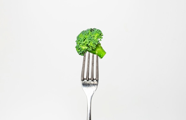 Fresh broccoli on fork isolated on white. healthy lifestyle