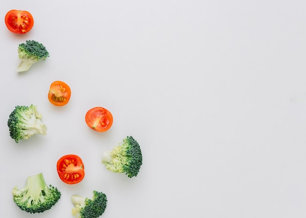 Fresh broccoli and halved red tomatoes on white background