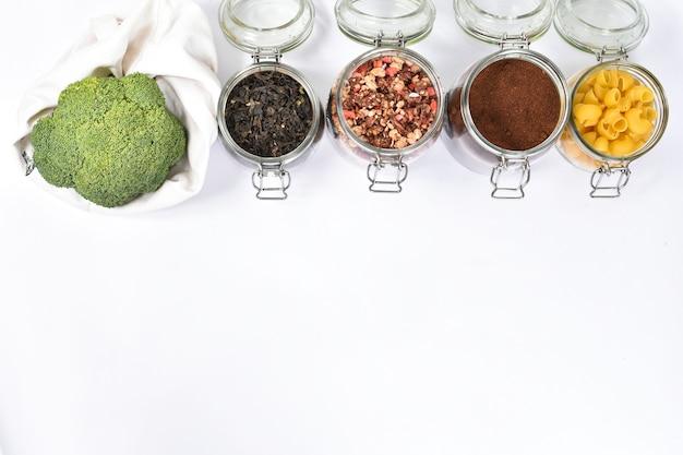 흰 벽에 에코 친화적 인 베이지 색 토트 백에 신선한 브로콜리. 녹차, 그라 놀라, 커피, 파스타와 함께 유리 항아리. 제로 폐기물 개념, 단호하게.