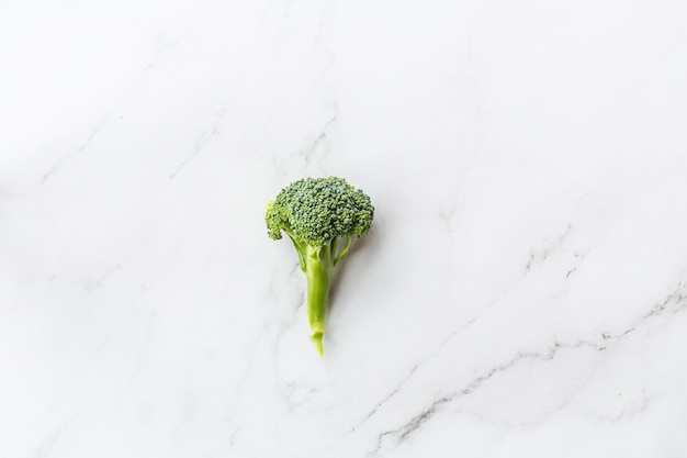 Fresh broccoli lying on white marble