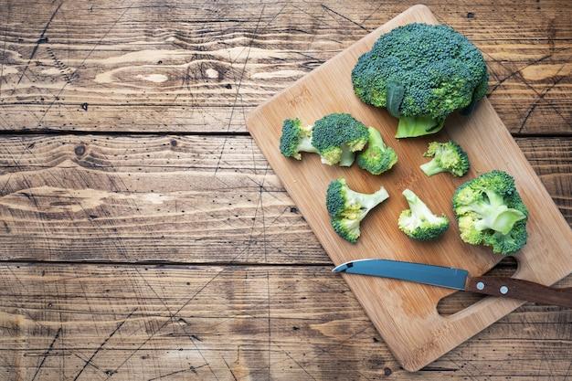 Fresh broccoli sliced on a wooden cutting board. copy space.