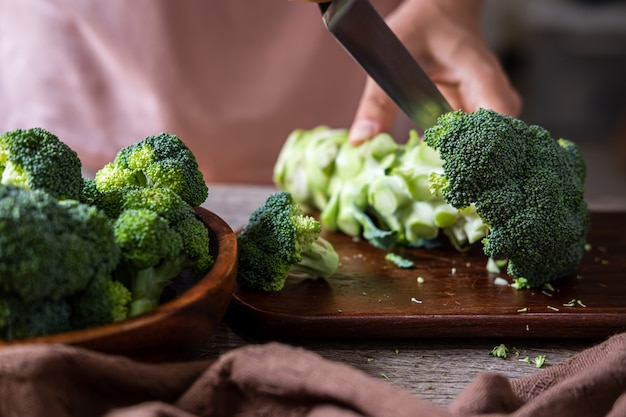 Fresh broccoli with wooden cutting board on old wooden table
