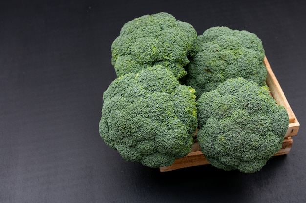 Fresh broccoli in wooden box on black surface green vegetables