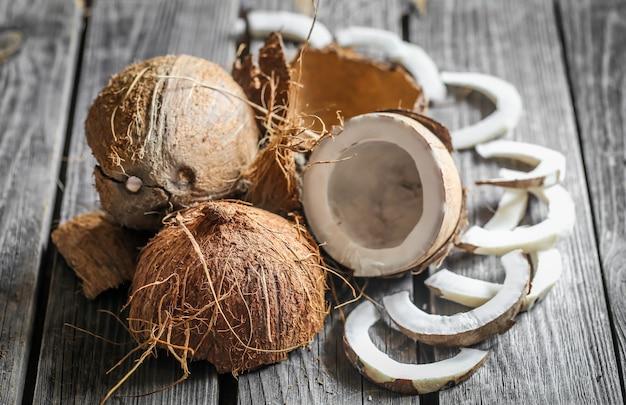 Noci di cocco rotte fresche sulla tavola di legno