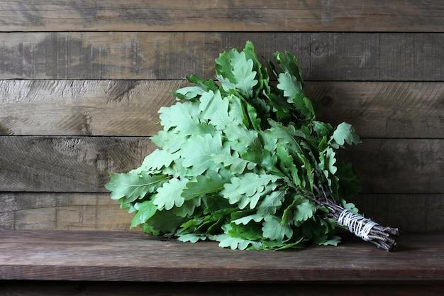 Свежий веник с дубовыми листьями на деревянном столе