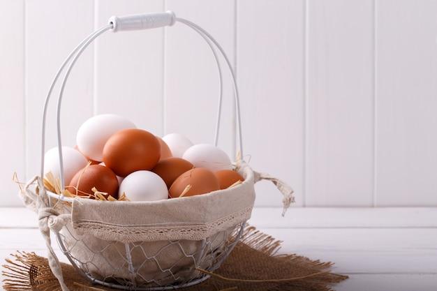 Свежие коричневые и белые куриные яйца в корзине на светлом деревянном столе
