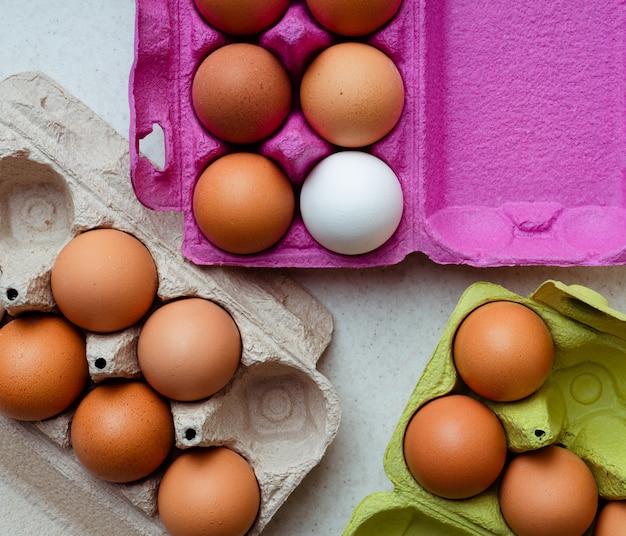 Свежие коричневые и белые яйца в разноцветных картонных контейнерах, вид сверху