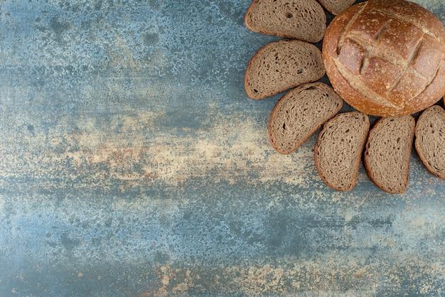Un panino marrone fresco con fette su sfondo di marmo