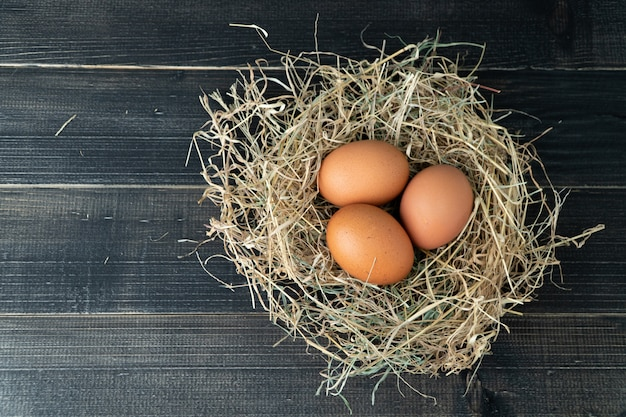 Fresh brown chicken eggs in hay nest on black wood