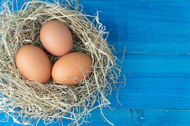 Fresh brown chicken eggs in hay nest on blue wooden background.