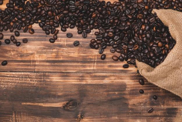 나무 바탕에 신선한 갈색 커피 콩입니다.