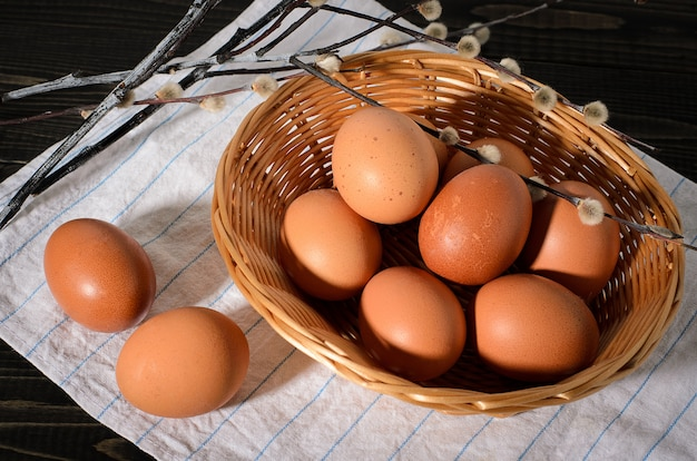 Fresh brown eggs on a rustic, wooden, black, dark background in a basket