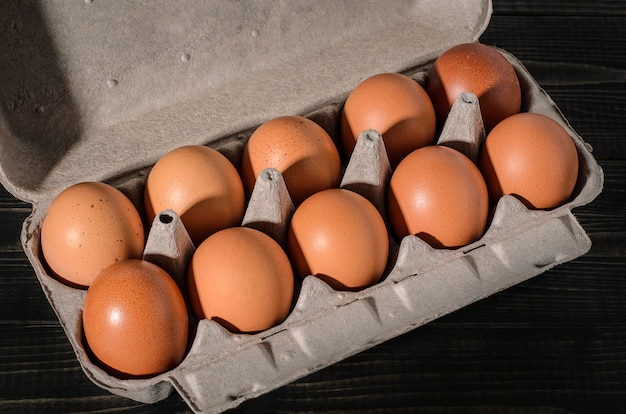 Fresh brown eggs on a rustic, wooden, black, dark background in a box