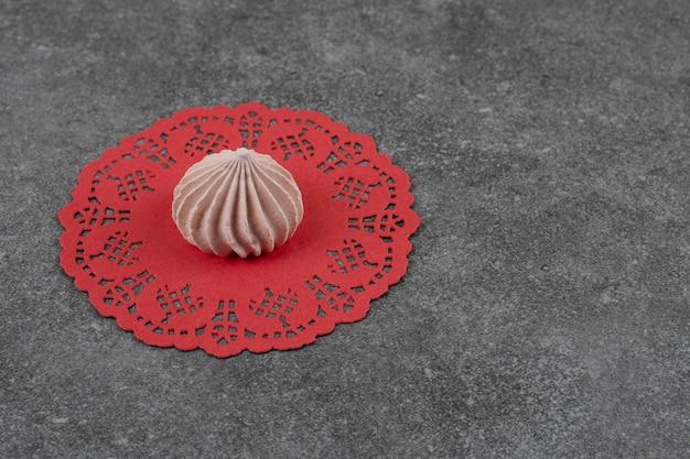 Biscotto di meringa marrone fresco sul tovagliolo rosso sulla superficie grigia.