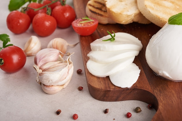 まな板にトマト、モッツァレラチーズ、バジルを添えた新鮮なブルスケッタ。伝統的なイタリアの前菜またはスナック、前菜。上面図。フラットレイ。チェリートマトのチャバタ。