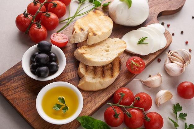 커팅 보드에 토마토, 모짜렐라 치즈와 바질과 신선한 브루스케타. 전통적인 이탈리아 전채 또는 간식, 전채 요리. 평면도. 평평하다. 체리 토마토를 곁들인 치 아바타.
