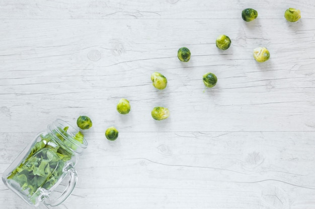 Fresh brussels sprouts and lettuce arranged with jar on wooden desk