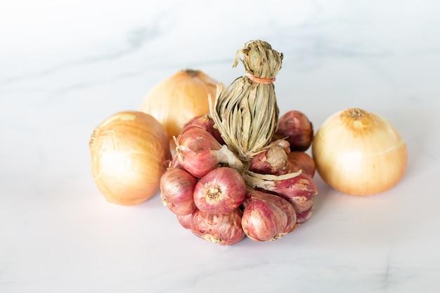 Fresh bulbs of onion on marble table