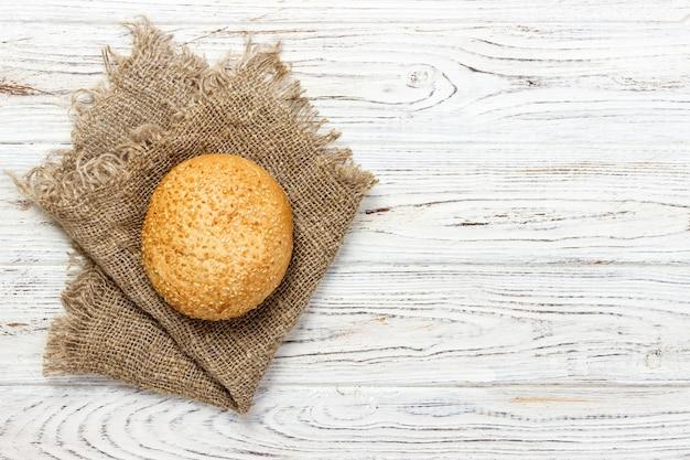 Свежая булочка с семенами на деревянном столе. вид сверху.