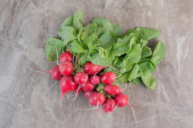 Свежий букет красной репы и листьев репы на мраморе.
