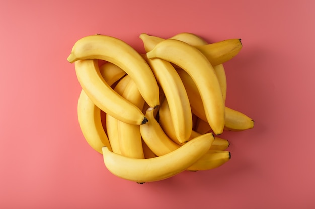 ピンクの背景に分離された黄色いバナナの新鮮な束。ミニマルなコンセプト。フリースペース