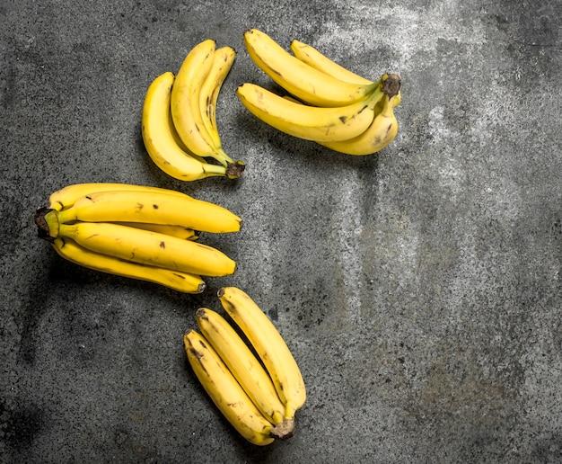 バナナの新鮮な束。素朴な背景に。